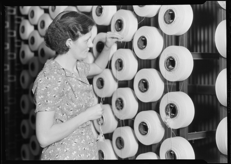 Millville,_New_Jersey_-_Textiles._Millville_Manufacturing_Co._(Woman_standing_at_large_spools_of_thread.)_-_NARA_-_518675.jpg