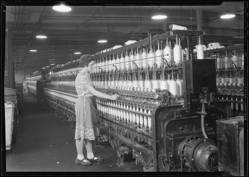 Millville,_New_Jersey_-_Textiles._Millville_Manufacturing_Co._(Woman_standing_at_long_row_of_bobbins.)_-_NARA_-_518676.jpg